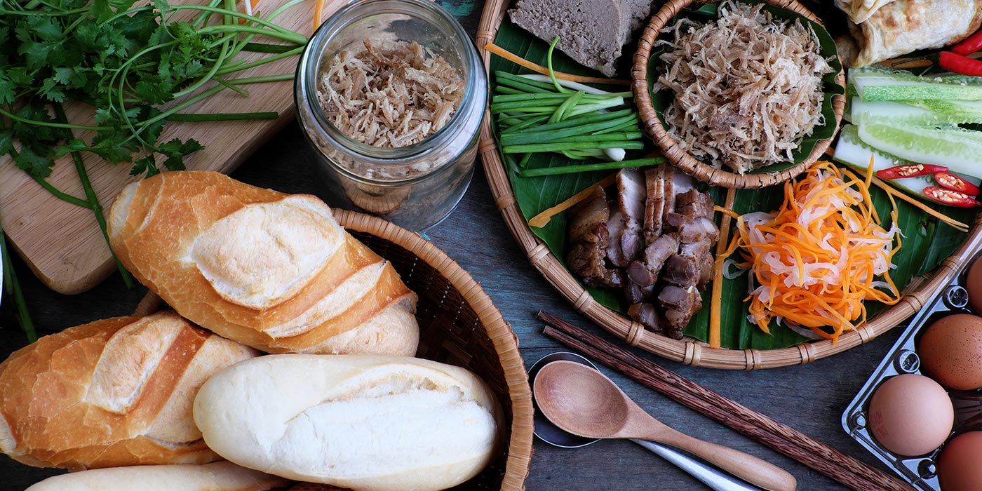 bread, cilantro, shredded carrots, pork, and other ingredients laid out for sandwiches