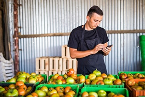 guy in front of his produce looking at his phone