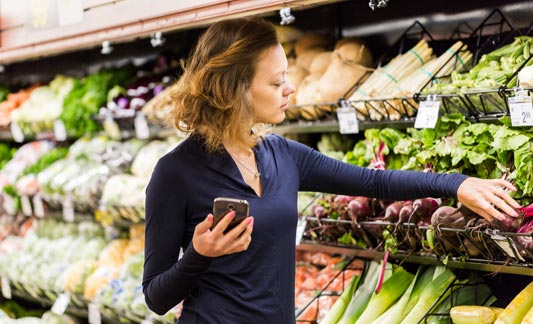 Woman holding phone and checking produce