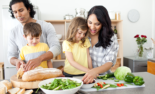 Family prepping produce to snack on in kitchen