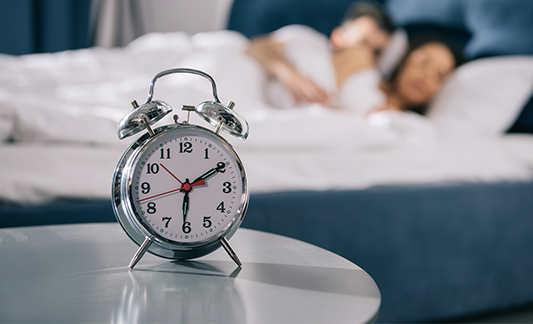 alarm clock with couple sleeping in background