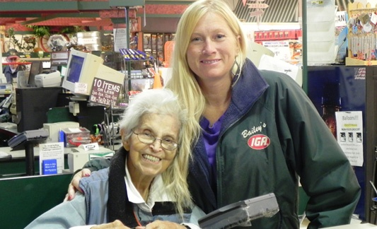 women in iga jacket posing with older woman in iga store