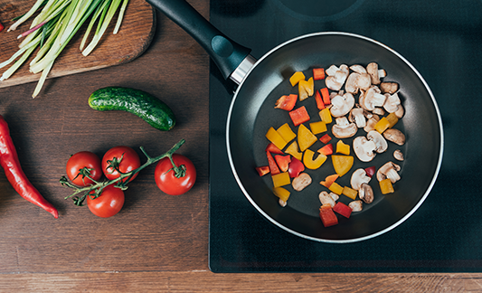 Veggies cooking in a skillet and on a table next to the stove