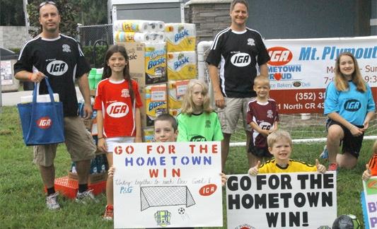 kids and IGA family members promoting hometown happenings