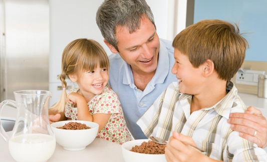 Father and children, smiling, and eating cereal