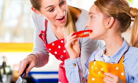 Mom and daughter eating a red pepper in kitchen
