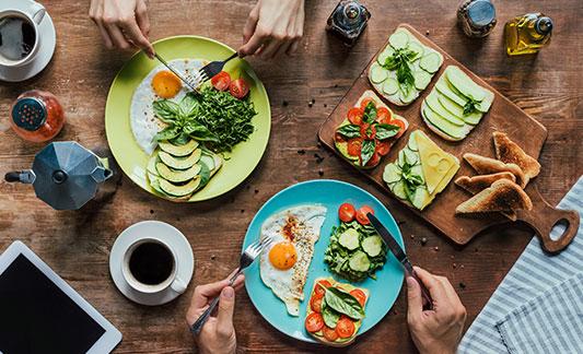 two plates of breakfast - eggs, veggies, toast, coffee.