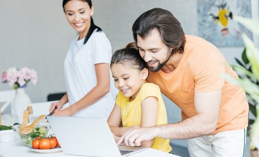 Family looking at laptop and cooking