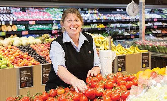 IGA employee organizing tomatoes