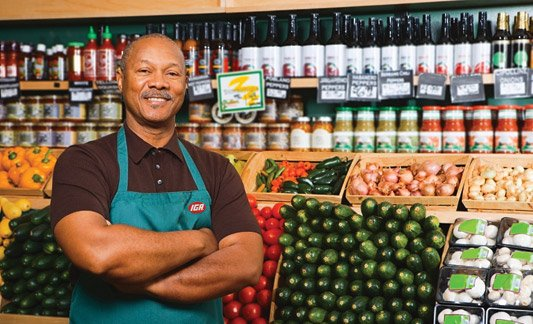 Man and IGA employee posing and smiling by the produce section