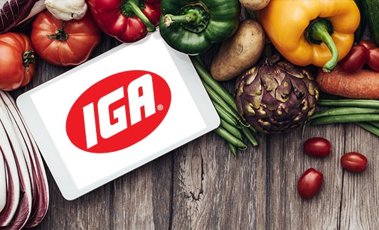 IGA logo on a tablet surrounded by produce on a table