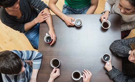 Group of people talking drinking coffee